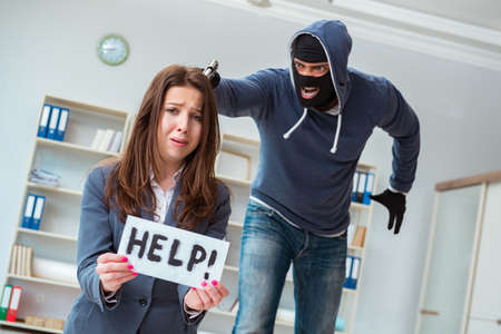 Criminal taking businesswoman as hostage in office Banque d'images