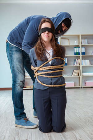 Criminal taking businesswoman as hostage in office Foto de archivo