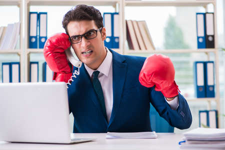 Businessman with boxing gloves angry in office 스톡 콘텐츠