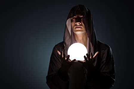 Young wizard with crystal ball in dark room Banque d'images