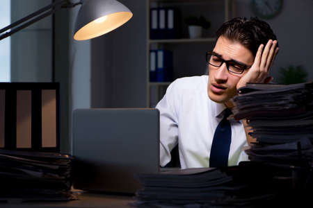 Young businessman working overtime late in office