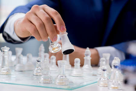 Young businessman playing glass chess in office Banque d'images