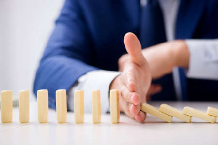 jeune homme d & # 39 ; affaires jouant avec domino dans le bureau