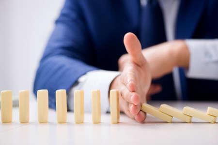 Młody biznesmen bawić się z domino w biurze