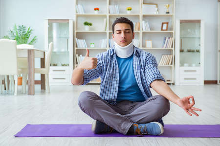 Man with neck injury meditating at home on floor 스톡 콘텐츠