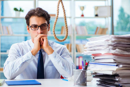Unhappy businessman thinking of hanging himself in the office