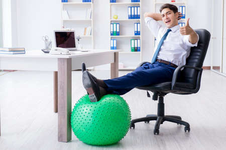 Young businessman doing sports stretching at workplace Stock Photo