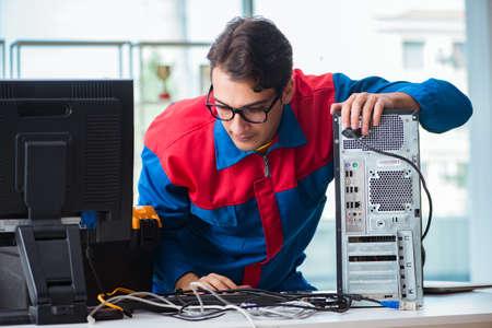 Computer repairman working on repairing computer in IT workshop Stock Photo