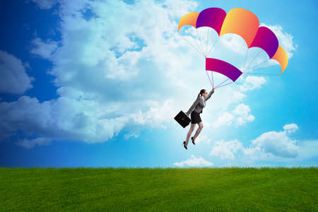 Businesswoman flying on parachute in business concept