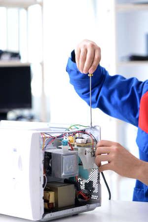 Young repairman fixing and repairing microwave oven Stock fotó