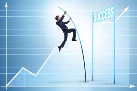 Businessman pole vaulting over towards his success career Foto de archivo