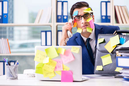 Businessman with reminder notes in multitasking concept Stockfoto