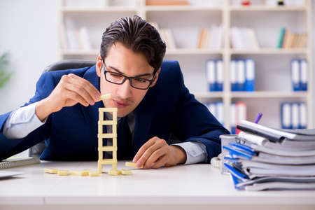 Young businessman building domino tower in office Stock Photo