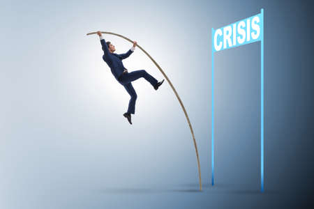 Businessman pole vaulting over crisis in business concept