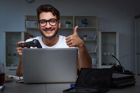 Young man playing games long hours late in the office Stock Photo