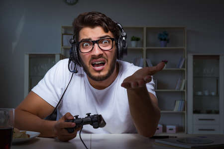 Young man playing games long hours late in the office Imagens