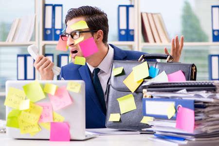 Businessman with reminder notes in multitasking concept Banque d'images