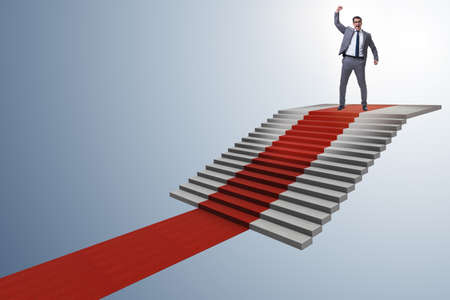 Young businessman climbing stairs and red carpet Banco de Imagens