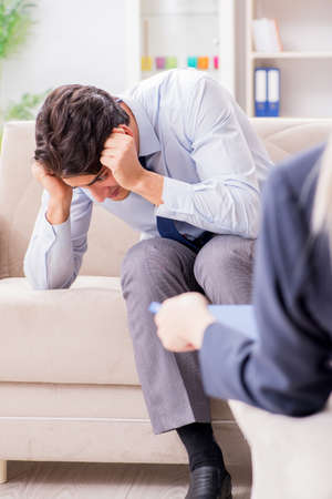 Young man visiting psychiatrist doctor for consultation Stock Photo