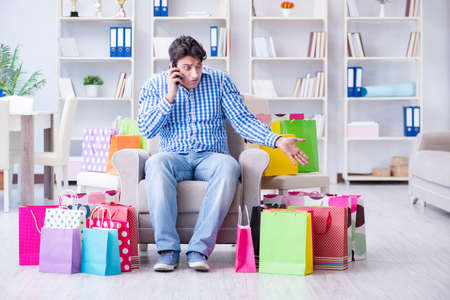 Young man after excessive shopping at home Stock Photo