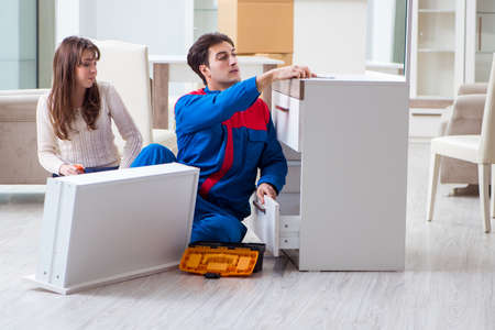 Contractor repairman assembling furniture under woman supervision Imagens