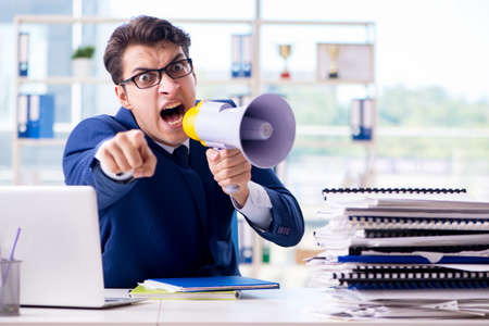 Angry aggressive businessman with bullhorn loudspeaker in office Stockfoto