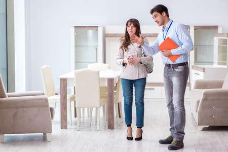 Salesman explaining to woman customer at furniture store
