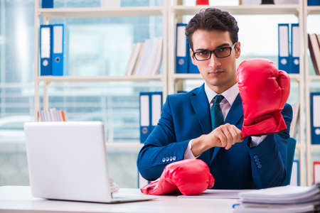 Businessman with boxing gloves angry in office Stock Photo