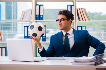 Businessman playing football in the office