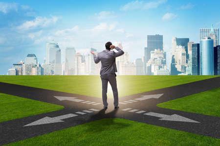 Jonge zakenman bij kruispunten in onzekerheidsconcept