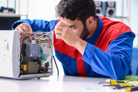 Young repairman fixing and repairing microwave oven 스톡 콘텐츠