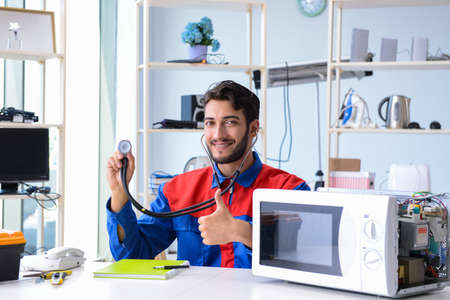 Young repairman fixing and repairing microwave oven Banque d'images