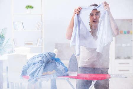 Inattentive husband burning clothing while ironing Imagens