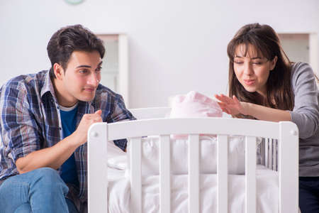 Stock photo young parents with their newborn baby near bed cot
