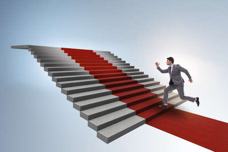 Young businessman climbing stairs and red carpet Stock Photo