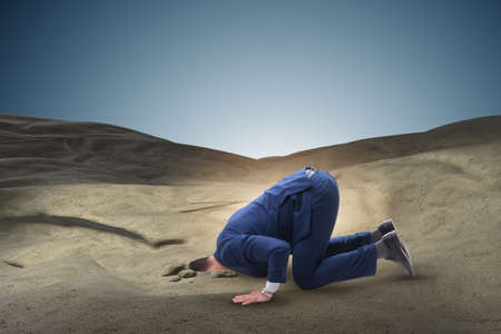 Businessman hiding his head in sand escaping from problems 스톡 콘텐츠