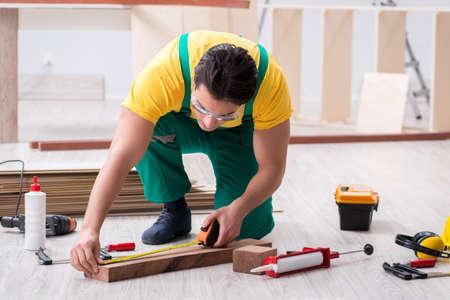 Empreiteiro trabalhando no piso de madeira laminado Foto de archivo - 94881198