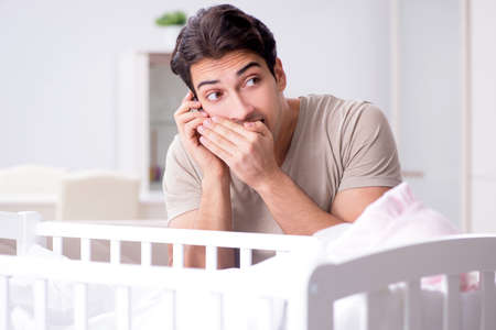 Young father enjoying time with newborn baby at home Фото со стока