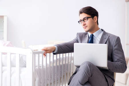 Young businessman trying to work from home caring after newborn