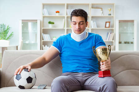Man with neck injury watching football soccer at home