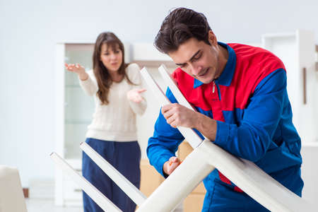 Contractor repairman assembling furniture under woman supervision Stock Photo