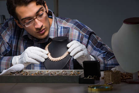 Young male jeweller working at night in his workshop Stock Photo