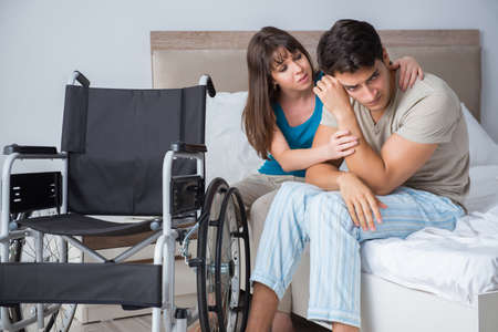 Desperate man on wheelchair with his sad wife