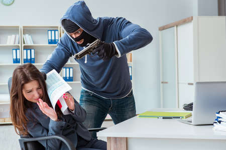 Criminal taking businesswoman as hostage in office Stock Photo