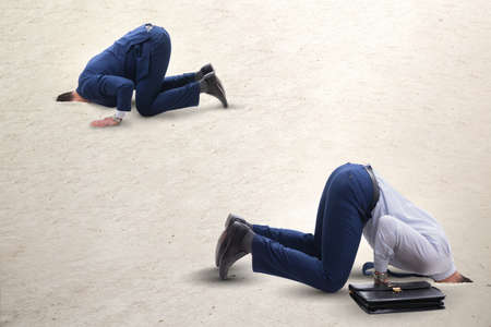 Businessman hiding his head in sand escaping from problems Banque d'images