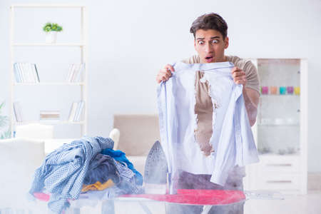 Inattentive husband burning clothing while ironing Stock Photo