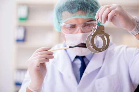 Criminologist police chemist looking at crime evidence