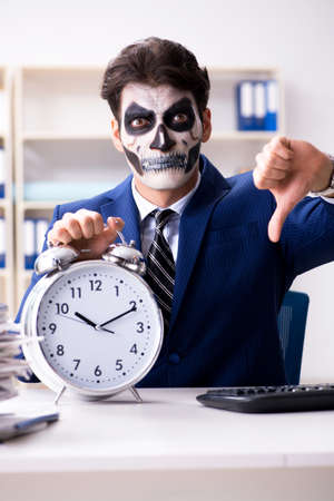 Businessmsn with scary face mask working in office Banco de Imagens