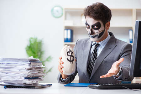 Businessmsn with scary face mask working in office Stockfoto