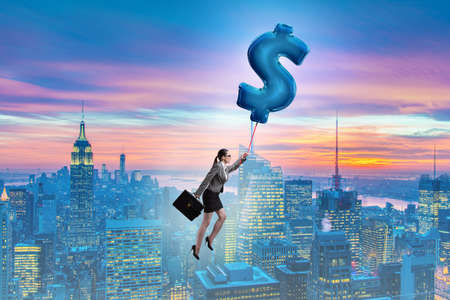 Businesswoman flying on dollar sign inflatable balloon